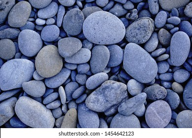 Multiple oval shape of stones. Gray-blue shade background. Top view.