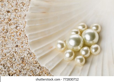 Multiple pearls in sea shell over sand background
