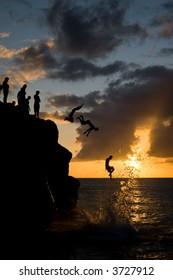 Multiple people jumping off a rock in Waimea Beach