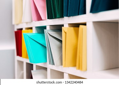 Multiple piles of various postal envelopes arranged on a shelf by color and type categories. Sorted paper mail covers in library/office.