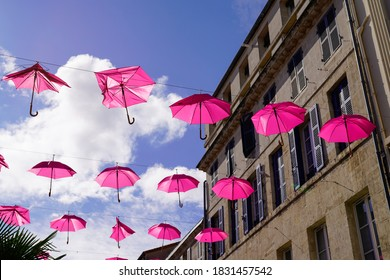 Multiple pink umbrellas hanging in october month over the street