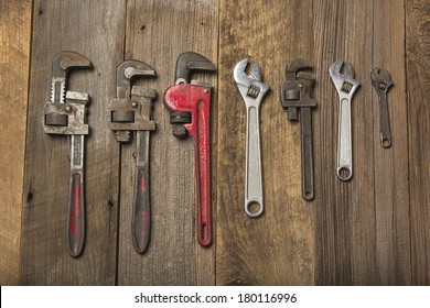 Multiple Pipe Wrenches On Wood Background