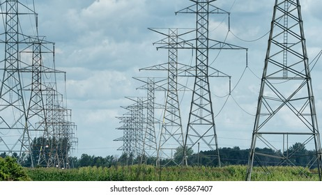 Multiple power lines in field on cloudy day.