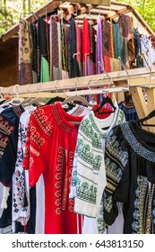 Multiple profile of romanian traditional costumes on hangers shown outdoors.