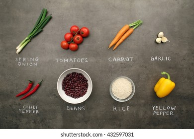 Multiple recipe ingredients and vegetables with chalky signs on grey kitchen table. Top view, flat lay food concept.