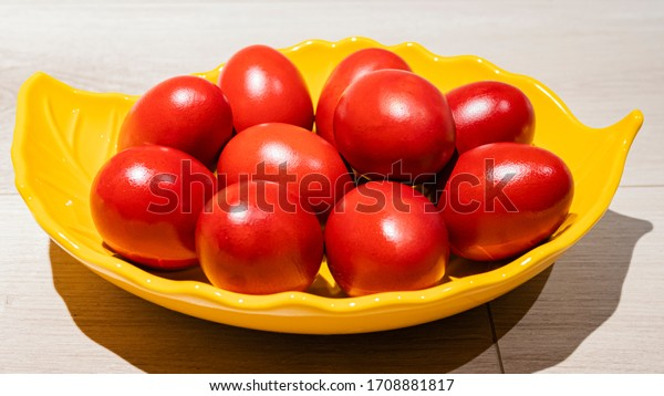 Multiple red eggs in a bowl, isolated on a wooden surface. Red eggs symbol of Easter in a yellow bowl.