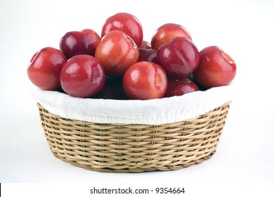 Multiple red plums against a white linen background.