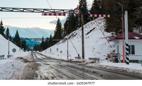 Multiple road signs on the snowy road, train trucks and boom barrier in the background