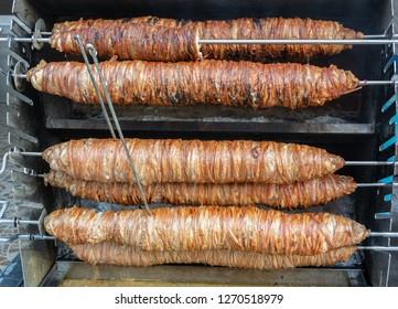 Multiple rolls of lamb intestines kokorec roasting on wood fire in Turkey.