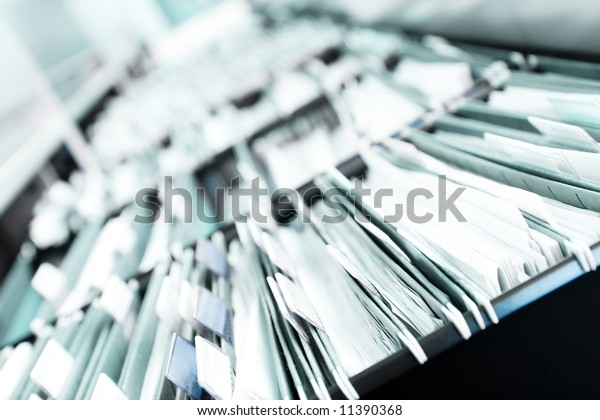 """Multiple rows of filing cabinets in an office or medical establishment, overflowing with files.  Narrow depth of field to emphasize the """"neverending"""" feeling"""
