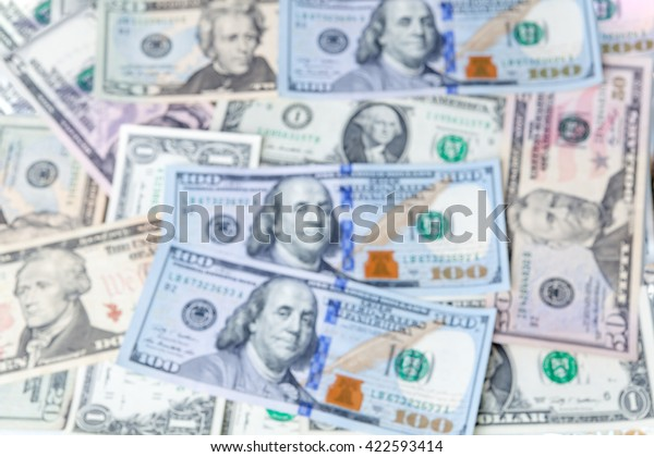 Multiple scattered American hundred dollar banknotes in full frame coverage with corner vignetting viewed from above in a conceptual financial background