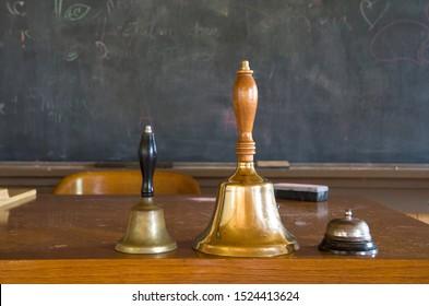 Multiple Sizes Schools Bells on Teacher's Desk with Blackboard in the Background Horizontal