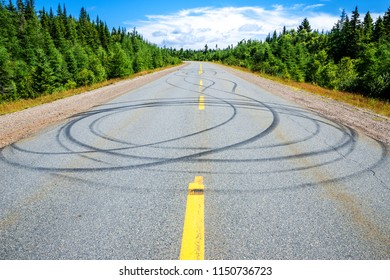 Multiple skid marks on a two lane highway.  Many circular marks. Trees line the road and the sky is mostky blue above. Bright sunny day.