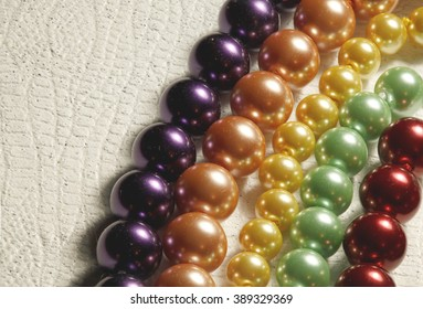 Multiple strands of colored pearls on a textured background