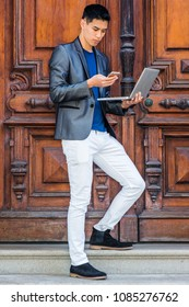 Multiple task. Young Asian American Man studying, working in New York, wearing gray blazer, white pants, black shoes, standing by old office door, working on laptop computer, texting on cell phone.