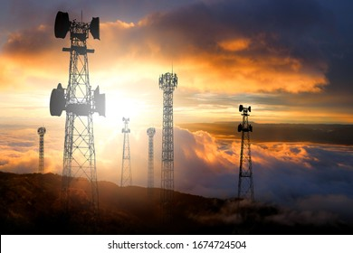 Multiple telecommunication antennas against the sunset background