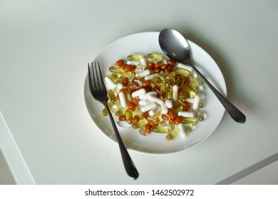 Multiple type of vitamins on white dinner plate with aluminum spoon and fork, for vitamin overuse concept, food supplement background