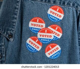 Multiple I Voted Today stickers on the blue denim working shirt collar for midterm elections in the USA