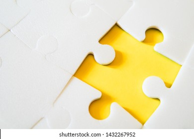Multiple white puzzle pieces put together without one piece. View from above.