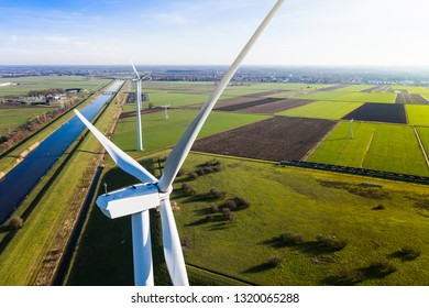 Multiple wind turbines generating eco friendly green energy for a better environment. Placed on fields next to a canal near Waalwijk, Noord-Brabant, Netherlands. Seen from above / birds eye view.