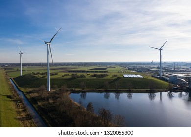 Multiple wind turbines generating eco friendly green energy for a better environment. Placed on fields next to a lake near Waalwijk, Noord-Brabant, Netherlands. Seen from above / birds eye view.