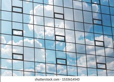 Multiple windows background with sky reflection. View of double glazed windows with sky reflection. Symmetry and texture. Windows background. Facade of a modern glass fronted building