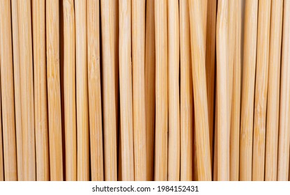 Multiple wooden bamboo skewers laying on white background macro Long wooden skewers for grilling or barbecue background image