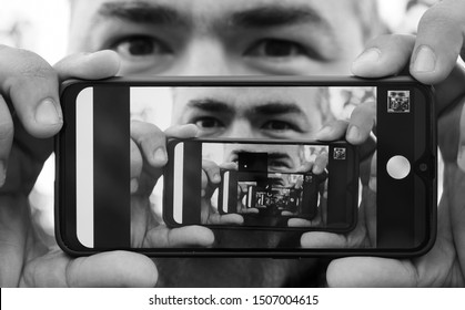 multiplying effect between two mirror surfaces. re-reflection of a male face in perspective. image in screen of mobile cell phone. man portrait