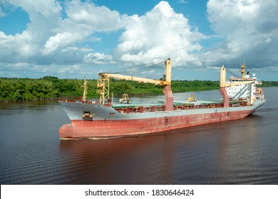 Multipurpose cargo ship underway in river delivering bulk cargo for international transshipment.
