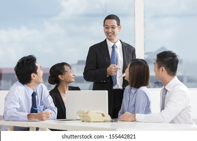 Multi-race business team working together around a laptop computer