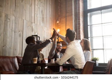 Multiracial best friends group giving high five sitting at cafe table, happy diverse african and caucasian young people join hands up together at meeting, unity and support in friendship concept