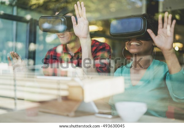 Multiracial best friends having fun wearing virtual reality glasses in cafe bar restaurant with glass reflection - Young people using new technology - New mania trends addiction - Raw warm filter