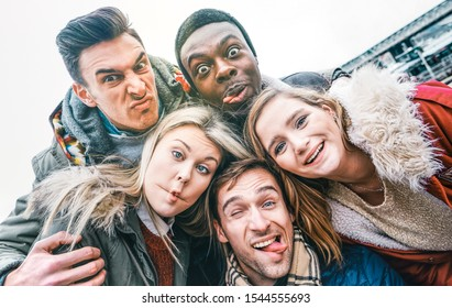 Multiracial best friends taking selfie outdoor on autumn winter clothes - Happy youth concept with millennial people having fun together - Multicultural friendship against racism - Bright vivid filter