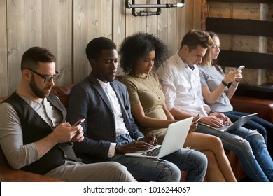 Multiracial black and white people sitting on couch ignoring each other immersed in phones and laptops, diverse young students obsessed with online apps using modern gadgets, devices overuse concept