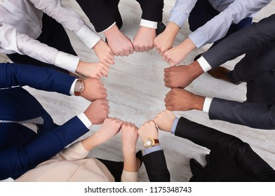 Multiracial business colleagues holding hands in circle, top view