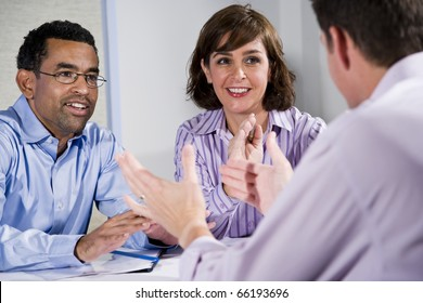 Multiracial business meeting in boardroom, sitting at a table