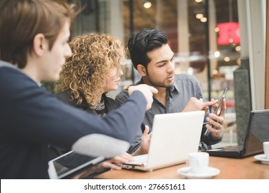 Multiracial business people working connected with technological devices at the bar