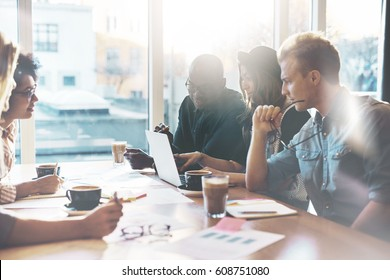 Multiracial business team made of young proficient employees sitting together in the meeting room of a modern company
