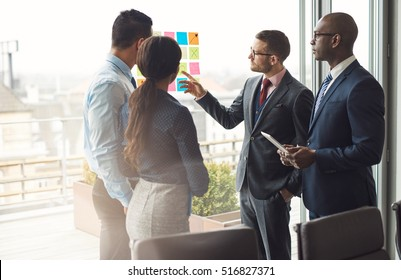 Multiracial business team standing brainstorming together in front of a large bright view window at the office pointing to a set of colorful memos on the glass