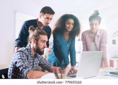 Multiracial business team working together around a laptop  in the meeting room of a modern company