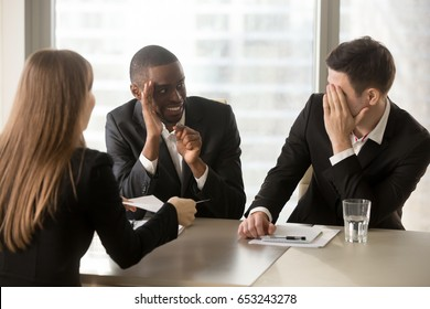 Multiracial businessmen hiding face with hands, sneaking look at each other while businesswoman presenting document, recruiters covertly discussing candidate, secretly whispering during interview