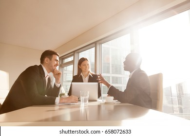 Multiracial businesspeople discussing idea, new business projects at conference table, multi-ethnic business group joking having fun, friendly atmosphere, pleasant funny conversation in sunny office