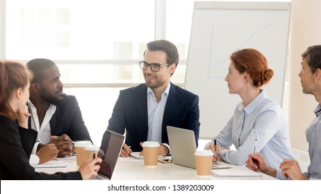 Multiracial businesspeople sit at office desk in conference room cooperating discussing company project, smiling millennial ceo hold team briefing talk brainstorm with employees at boardroom meeting