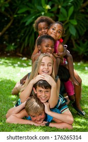 Multiracial children playing together forming human pile in garden.