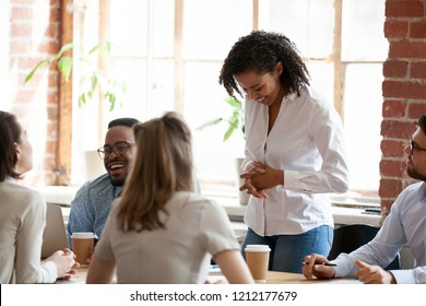 Multiracial colleagues talk during coffee break at business meeting, diverse millennial employees have casual conversation chatting at briefing, workers joke and laugh in coworking loft office