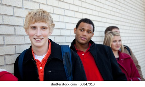 Multi-racial college students/friends outside against a brick wall