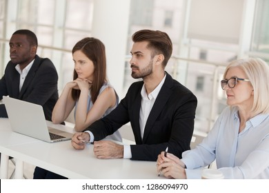 Multiracial company representatives sitting at desk in modern office boardroom during job interview. Colleagues headed by boss attentive listening candidate for the position. Human resources concept
