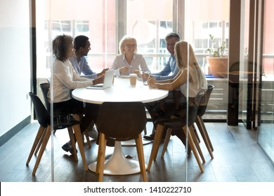 Multiracial company staff laughing talking at group meeting in modern office room at conference table, corporate diverse team employees discussing work at team multi ethnic briefing behind glass door