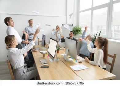 Multiracial corporate team of young and senior business people launching paper planes together in office, diverse motivated employees group laughing having fun at work, teamwork common goals concept