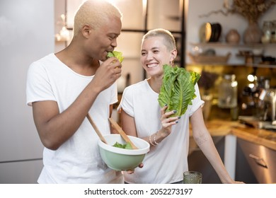 Multiracial couple eating organic salad at home kitchen. Idea of healthy eating. Concept of relationship. Modern domestic lifestyle. Black man and european girl spending time together